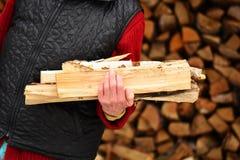 Gammal kvinna med vedträ i händerna i byn Arkivbild