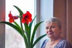 Gammal kvinna och blomma Arkivbild