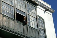 Gammal kvinna på hennes fönster av henne ett hus i Santa Cruz Arkivbilder