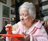 Gammal kvinna som äter en skiva av bröd Fotografering för Bildbyråer