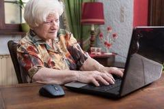 Gammal kvinna som använder en bärbar dator Arkivbild