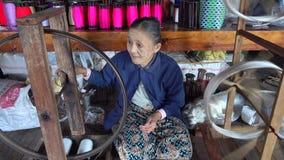 Gammal kvinna som arbetar på textilfabriken i Myanmar lager videofilmer