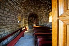 Gammal kvinna som ber i tomma den medelhavs- bykyrkan royaltyfria bilder
