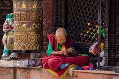 Gammal kvinna som ber på Bodnathen Stupa Royaltyfria Foton