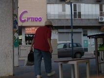 Gammal kvinna som går med en påse på en stads- trottoar i ett bostadsområde i staden royaltyfria bilder