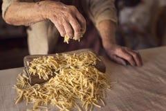Gammal kvinna som gör hemlagad pasta royaltyfria foton