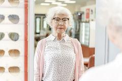 Gammal kvinna som kastar en blick på spegeln Arkivfoton