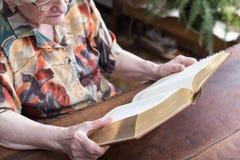 Gammal kvinna som läser en bok Arkivfoto