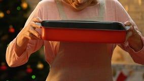 Gammal kvinna som luktar nytt bakade pepparkakakakor, julatmosfär stock video