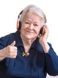 Gammal kvinna som lyssnar till musik i hörlurar Arkivfoton