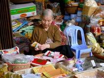 Gammal kvinna som räknar pengar i hennes stall på en lokal marknad Arkivbild