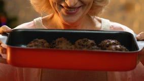 Gammal kvinna som rymmer nytt bakade muffin, feriefester, jultraditioner arkivfilmer