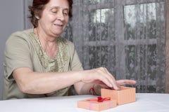 Gammal kvinna som ser gåvaasken som accepterar gåva fotografering för bildbyråer