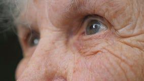 Gammal kvinna som ser in i avståndet Ögon av en äldre dam med skrynklor runt om dem Slut upp ståenden av farmodern lager videofilmer
