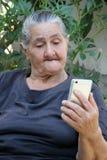 Gammal kvinna som ser på en smartphone royaltyfria foton