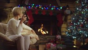Gammal kvinna som sitter med ett exponeringsglasvin vid julgranen lager videofilmer