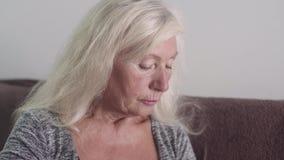 Gammal kvinna som sitter och ser det hemmastadda rummet för sida, ledsen farmorstående på den vita färgbakgrunden ensamt lager videofilmer
