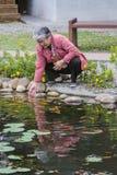 Gammal kvinna som spelar fiskpoolsiden Fotografering för Bildbyråer