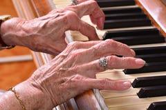 Gammal kvinna som spelar pianocloseupen royaltyfria bilder