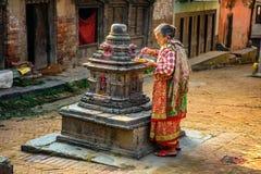 Gammal kvinna som tänder en stearinljus i gatan av Katmandu, Nepal Royaltyfri Foto