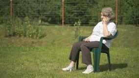 Gammal kvinna som talar genom att använda en mobiltelefon utomhus lager videofilmer