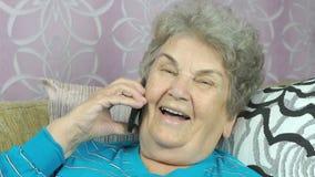 Gammal kvinna som talar med dottern på mobiltelefonen arkivfilmer