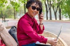 Gammal kvinna som talar p? en mobiltelefon och smilling royaltyfri foto