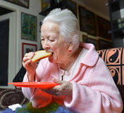 Gammal kvinna som äter en skiva av bröd Royaltyfria Bilder