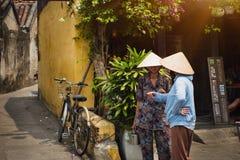 Gammal kvinna som två talar på gator av Hoi An den gamla staden Royaltyfria Foton