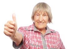 Gammal kvinna som visar det ok tecknet på en vit bakgrund Fotografering för Bildbyråer