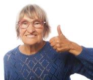 Gammal kvinna som visar det ok tecknet på en vit bakgrund arkivbild