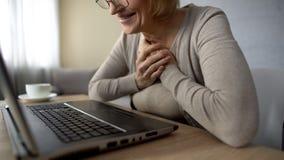 Gammal kvinnlig som glädjas för att tala till barn i internet som ser bärbar datorskärmen fotografering för bildbyråer