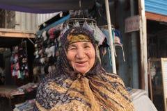 Gammal kyrgyz kvinna i traditionell klänning Arkivfoton