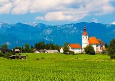 Gammal kyrka i fältet Liten by i Slovenien Royaltyfri Bild