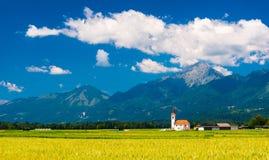 Gammal kyrka i fältet Pittoreskt landskap med berg Arkivfoto
