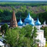 Gammal kyrka med blåa kupoler på bakgrunden av skogen till slättarna som lämnar bak horisonten Arkivfoton