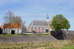 Gammal kyrka med en kanon i Schokland (Unesco), en tidigare ö i Noordoostpolderen, Nederländerna Arkivfoto
