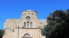 Gammal kyrka med trädet och blå himmel i sommar arkivbild