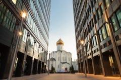 Gammal kyrka mellan två kontorsbyggnadar Fotografering för Bildbyråer