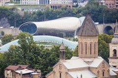 Gammal kyrka och modern bro i Tbilisi Royaltyfri Bild