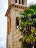 Gammal kyrklig clocktower med en stor palmträd framme av den, Kreta, Grekland arkivfoton