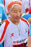 Gammal löpare i internationell maraton i Xiamen, Kina, 2014 Arkivbild
