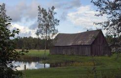 Gammal ladugård bredvid ett damm i landet i Lettland Royaltyfria Bilder