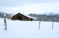 Gammal ladugård i snön Arkivbild