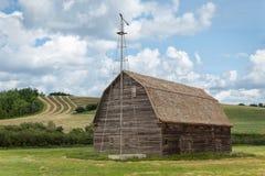 Gammal ladugård med ett fåfängt för väder Royaltyfri Bild