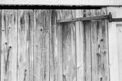 Gammal ladugårddörr med ett rostigt metallgångjärn Royaltyfri Bild