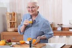 Gammal lady som gör orange fruktsaft. Arkivbild