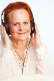 Gammal lady som lyssnar till musik Fotografering för Bildbyråer