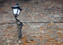 Gammal lampa på en texturerad tegelstenvägg arkivfoto