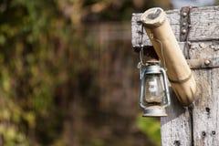 Gammal lampa som hänger på trähållaren royaltyfri fotografi